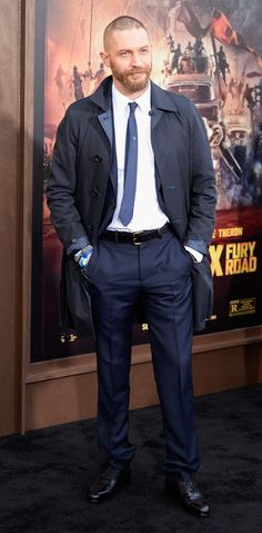Tom Hardy attended the Los Angeles premiere for his latest movie, Mad Max: Fury Road. Wearing a navy two-button suit from Alexander McQueen, Hardy finished his classic look with a sharp trench coat.