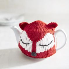 Serving up a spot of whimsy, our fox sweater-clad teapot keeps your favorite brew warm and cozy. Charming knitted fox (complete with perked-up ears and flirty eyelashes) covers the classic white stoneware teapot like a soothing embrace until you're ready to pour.