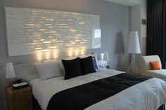 Modern headboard. Could replicate this with MDF.  I think what makes it so cool are the lights shining up on it.