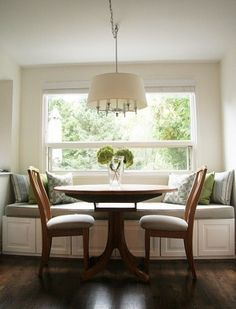 a built-in banquette is flankedtall glass cabinets for storing
