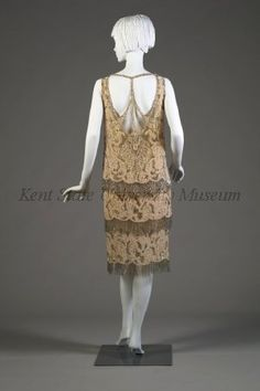 Dress, 1920s, French, donor attributed to Worth. Peach/skin tone silk dress with panels below waist. Beautifully adorned with silver bugle beads, rhinestones and pearls. Heart shape motif at center front skirt. Back of dress is open with T-straps across shoulders and down . Back
