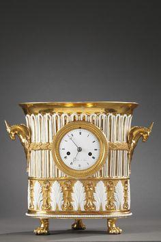 """Une intéressante pendule en forme de vase en porcelaine dorée, signée """"Normant à Paris"""", ornée sur le pourtour de cannelures rehaussées de feuillages et de petites perles avec en partie basse, un bandeau décoré d'une alternance de feuilles d'acanthe et de fleurettes surmontées de coquilles. Deux petites anses en forme de licornes. Cadran en émail avec chiffres romains, aiguilles Breguet en acier, indiquant les heures, les quarts d'heure et les minutes. Piétement à trois pieds griffe. c.1810"""