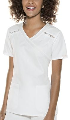 """Baby Phat Mock Wrap Top in White This mock wrap top features a hint of lace along the neckline and at front yoke with stitched down pleats. Two rounded patch pockets, side vents, and back elastic for shape. Center back length: 26"""".  Fabric: Brushed Cotton/Poly Poplin $26.99 #scrubs #nurses #doctors #medicaloutlet #babyphat Baby Phat Scrubs, Scrub Life, Nurses, Doctors, Poplin, Chef Jackets, Neckline, Pockets, Shape"""
