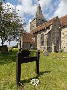 This is the beautiful church of St Mary in the Marsh in Kent. It is built on the site of an earlier Saxon church and dates from 1133. In the foreground is the modest grave of Edith Nesbit, author of many books including the famous children's book The Railway Children. Photograph by B Lowe