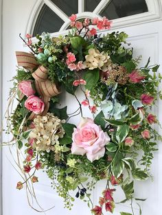 This sweet wreath is designed with lovely shades of blush pink roses, pink cherry blossoms, cream hydrangea, pale blue hydrangea and flowering vines. A mix of realistic garden foliages, including ferns, trailing ivy, seeded eucalyptus and sweet annie gives this lovely wreath a soft,