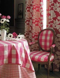 LOVE the bright pink buffalo check, the large scale floral and the curvy chair at this breakfast table