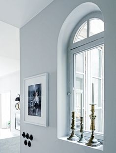 House tour: a modern French apartment within an opulent 19th-century shell: Moroccan brass candleholders add glamour to a simple window ledge in one of the corridors. The photo, by Rip Hopkins, was acquired at Galerie Le Réverbère in Lyon.