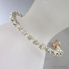 Wire wrapped crystal chain bangle. The base frame for this swarovski crystal cup chain bangle is made from sturdy gauge copper wire which was forged and hardened by hammer into the bangle to retain it