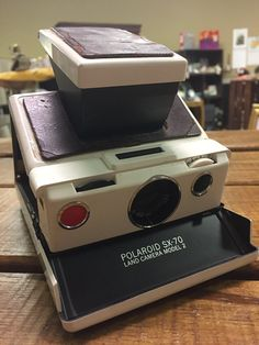 Vintage Polaroid SX-70 Land Camera w/ film speed meter & print coaters - in fair vintage condition. Has not been tested for working condition due to lack of film for this camera. However, has all working parts intact. Camera opens and closes easily and the all of the latches are in working order. Product is displayed in found condition.