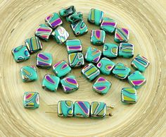 Color: Opaque Turquoise Green / Zebra Peacock / Vitrail  Size (mm): 6mm x 6mm  Hole size (mm): 1mm (approximately)  Shape: Tile Beads / Two Holes Beads / Square Flat Glass Beads / Czech Flat Square Beads  Sold in packs of 20pcs  peacock square beads, striped square beads, czech peacock beads, 6mm turquoise beads, striped tile beads, czech square beads, peacock tile beads, czech glass beads, 6mm vitrail beads, 6mm peacock beads, czech flat beads, 6mm square beads, czech tile beads, two hole…