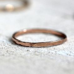 14k solid yellow gold hammered ring. Thin, delicate but super strong hand hammered wedding ring or everyday ring that can be worn as a single ring or stacked. A simple ring that makes a big statement. This listing is for ONE ring. The ring measures about 1.2mm wide.The ring is available in solid 14 karat pink gold (shown in the photos), solid 14 karat white gold or 14k solid yellow gold. These rings are made entirely from eco-friendly recycled gold by me in my San Diego, California studio.