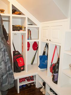 This mudroom utilizes unused space under the stairs to provide room for cubbies and hanging space, as well as shelving for shoe storage.