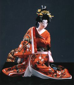 A dancer in a kimono adorned with embroidered plum branches and flowers. Plum trees, which bloom in winter and are associated with resilience and loyalty, are common motifs in Japanese art.
