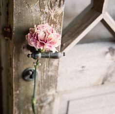 Pink flower on rustic doorknob. Wooden door