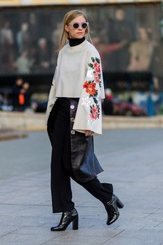 Pictured at Moscow Fashion Week, this show-goer's super-sized sleeves with appliquéd embroidered roses and metallic stars up the ante of her top-to-toe black outfit