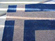 All home improvement stores sell big indoor/outdoor rugs. They're cheap and they're not attractive–dare I say ugly? Well, here's a way to make one of those utilitarian things look fabulous.What you need:One indoor/outdoor rug. Mine is an Ozite, 6' x 8' rug in bark. It cost 12 bucks and I had a 2 dollar rebate. If this size is too big, you can cut them down with a scissors to any size or shape you desire–probably even puzzle pieces. Paint that will work in outdoor applications. I used…