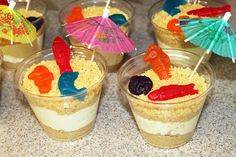 Cute beach or ocean themed snack for kids... Pudding with crushed graham crackers and umbrellas and swedish fish.