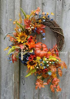 "Fall Wreath, Autumn Wreaths, Pumpkin Wreath, Thanksgiving Wreath, Country Harvest Wreath, Fall Woodland Wreath, Designer Fall Wreath Vermont Countryside Pumpkin Wreath. A cascade of gorgeous Sunflowers, Hydrangeas, Mums and other Fall flowers, mingle with colorful leaves, ferns, meadow grass, wheat, berries, fox tails and wildflowers in the seasons loveliest hues, gracing the edge of a rustic grapevine frame. Nestled among the beautiful flowers and posh foliage sits a quaint 6.5"" pumpkin…"