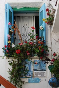 Charming window with lots of blue and flowers in Naxos, Greece