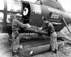 An Air Rescue Service crew treats a wounded UN soldier on one of an H-5G  helicopter's two outboard litters somewhere in Korea during the Korean War.