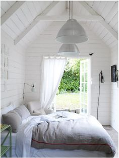 The bed looks super comfy. Loving the sloped ceiling and the wooden white walls.