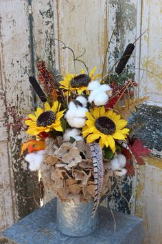 A rustic fall / autumn harvest silk arrangement with sunflowers, cotton, a burlap hydrangea, cattails, berries, pinecones and assorted foliage in a galvanized watering can. Two faux pheasant feathers and grasses cascade out of the metal container. A jute twine bow is tied to the handle of the watering can. This arrangement is ready to ship now and would be great for your rustic fall and autumn decorating. It measures approximately 22 inches tall and 18 inches wide. ***props not included....