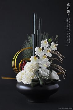 metallic wire loops contrast with black vertical bamboo and container. round blooms repeat wire loops