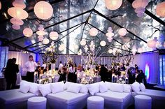 Clear tent with paper lanterns, pipe & drape, and white lounge furniture. Looks great!