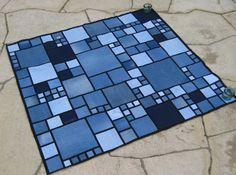 Com jeans velhos empilhados alguns pares, você pode costurar o tapete. Esse tapete consiste em cortar vários quadrados diferentes e ir distribuindo no chão antes de costurar Para que ele fique bonito,