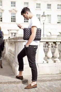 Shop this look on Lookastic:  http://lookastic.com/men/looks/crew-neck-t-shirt-zip-pouch-watch-jeans-tassel-loafers/5617  — White Crew-neck T-shirt  — Black Quilted Leather Zip Pouch  — Silver Watch  — Charcoal Jeans  — Brown Suede Tassel Loafers