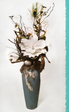 ELEGANT MAGNOLIA FLORAL // A beautiful floral arrangement with peacock and pheasant feathers, displayed in a turquoise and distressed white pottery vase.