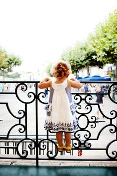Those curls, the sweet dress.  And that black wrought iron railing.