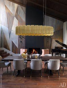 """Двусветная столовая — самое торжественное помещение в доме. Роспись стены выполнила художница Наташа Марсель. Наполу— американский орех, компания """"Золотой лес"""". Люстра, Delightfull. Стулья, Protocol. Рояль появился в комнате поинициативе хозяина— оннередко приглашает музыкантов, когда устраивает вечера для друзей."""