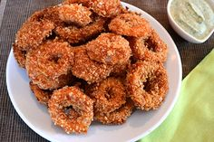 Rojo Onion Rings...onions are triple-dipped in non-dairy buttermilk, garlicky Sriracha-ketchup sauce, and panko breadcrumbs, then fried. Yes, please.