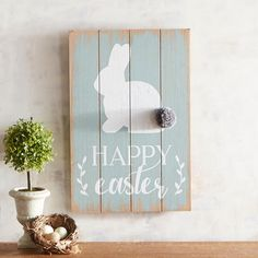 """A white bunny with a cotton pompom tail headlines our """"Happy Easter"""" wooden plank sign, reminding us that it's never too early to prepare for spring."""