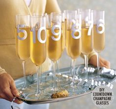 51 DIY ideas for New Year's Eve- like countdown champagne glasses by spray-painting numbers on them.