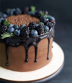 Beautiful rustic chocolate drippy cake. See how the blue hues from the berries are reflected in the shiny chocolate ganache? SO inviting!