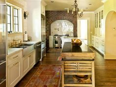 Hardwood floors and weathered brick contribute to the timeless design in this kitchen by Cyndy Cantley, CKD. A deep farmhouse sink is as practical as it is pretty, and a rough-hewn island keeps the look down to earth.