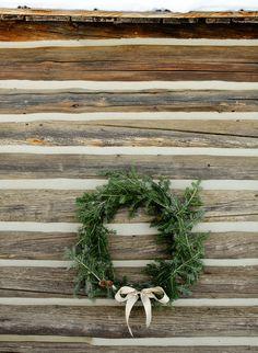 christmas wreath on log wall