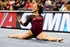University of Denver gymnast Maggie Laughlin smiles while holding the splits during her floor routine. Photo taken on March 14, 2015, at the University of Arizona.