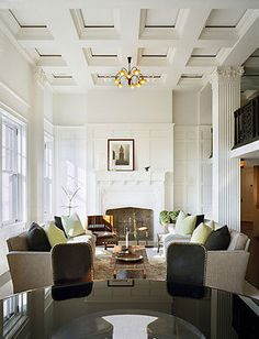 This NYC penthouse has ultra high ceilings, coffered ceilings, square columns, a second floor balcony, neutral furniture, a large fire place, and ornate wall details.
