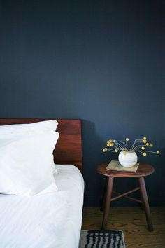 Modern bedroom with a navy blue contrast wall, white bedding, and a small wooden side table