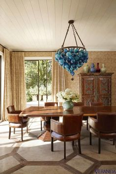 An azure pendant from Tobi Tobin complements chairs from Mecox, a table from Martyn Lawrence Bullard, and an antique Dutch cabinet in this sumptuous dining room. -Veranda