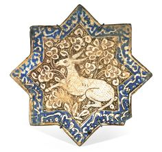 A Kashan lustre pottery star tile, Persia, circa 1300 eight-pointed stellar form, decorated in lustre over an opacified tin glaze with inglaze cobalt blue, featuring an onager within a ground of foliate sprays, enclosed by a border of calligraphic decoration, old collection label to reverse