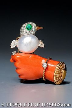 CARTIER, PARIS  An amusing emerald, diamond, coral and pearl novelty clip brooch,  mounted in platinum and 18 karat gold. A double prong brooch fitting with clasp.  French, circa 1960