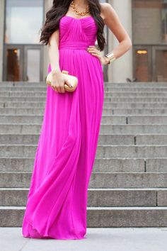 This dress looks like it is satiny because of the way it flows on her body. The dress is magenta (pink). The neck line is a soft v-neck and strapless. There is emphasis on her bust and a little above her waist.