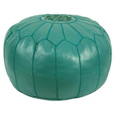 Showcasing a Moroccan-inspired arch motif and teal hue, this handmade faux leather pouf is perfect as an extra seat or an exotic footrest.