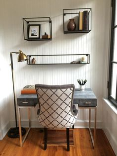 This contemporary office space is a perfect example of how to liven up a small space. Mounted 3D shelves allow for decorative display without taking up needed desk space. The distressed gray finish on the desk looks gorgeous against the pristine white paneled walls. An upholstered chair with nailhead trim adds a simple pattern to finish the look.