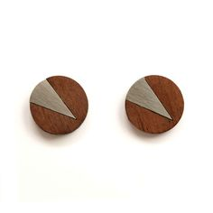 Turpentine Cate Earrings Walnut & Brushed Steel: These Cate Walnut & Steel Earrings are part of a brand new mixed material jewellery collection designed in-house by Jude de Berker and exclusive to the Turpentine.  Inspired by time spent in her dad's carpentry workshop as a child and her training as a jeweller at Central Saint Martins the range mixes solid walnut wood with brushed steel, copper, brass and 100% solid silver earrings backs and findings.  The design incorporates elegant…