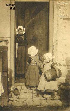 Terug van de bakker / back from the bakery, ca. 1910. Twee meisjes in klederdracht met elk een 8-ponder brood onder de armen. De vrouw in de deuropening is Bet van de Broeke.  Elisabeth van de Broeke was melkventster.